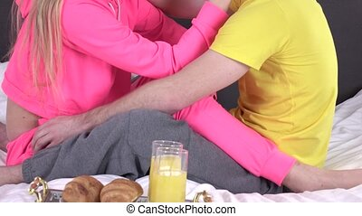 Beautiful young couple having breakfast in bed, cam moves...
