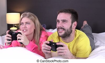 Happy young couple playing videogames in bed, great blonde...