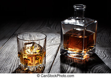 Backlit glass of whiskey with ice on wooden table
