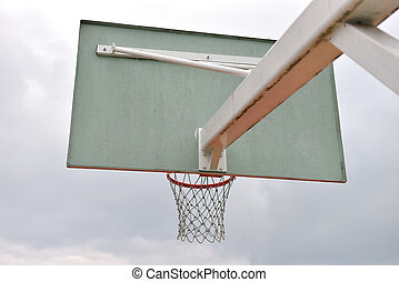 Behind of basketball board under cloudy sky in a school yard. Concept of kids playing outside. Team game. Outdoor games