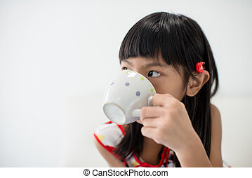Asian girl holding a cup of milk at home.