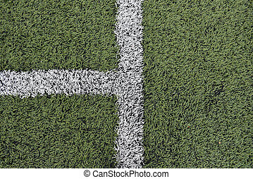 Detail of crossed white lines on football playground. Closeup of lines in a soccer field. Plastic green grass ground rubber. Background