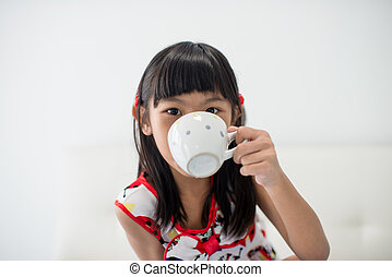 Asian girl holding a cup of milk at home