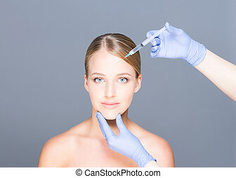 Doctor injecting botox in a beautiful face of a young woman...