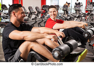 Male friends talking and having fun in a gym - Two young men...