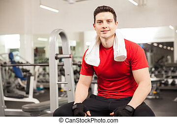 Hispanic man taking a break at the gym - Good looking young...