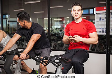 Young man using a smartphone at the gym - Portrait of a...