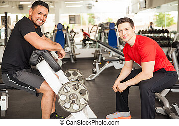 Men lifting some weights at the gym - Portrait of two young...