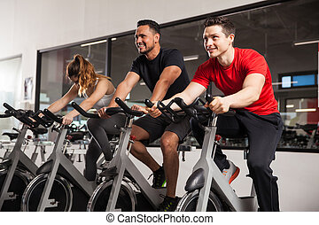 Male friends enjoying spinning in a gym - Two young male...