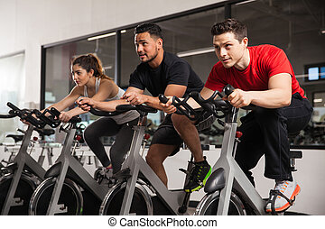 People doing some spinning at a gym - Three young people...