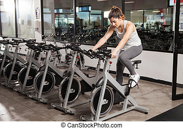 Beautiful girl doing spinning at the gym - Full length view...