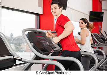 Man and woman running at the gym - Profile view of a young...