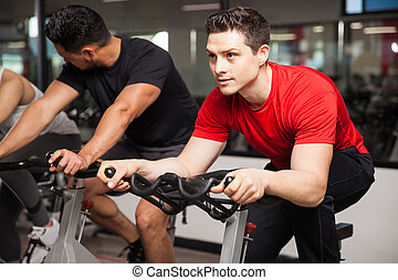 Handsome man doing some spinning in a gym - Portrait of an...