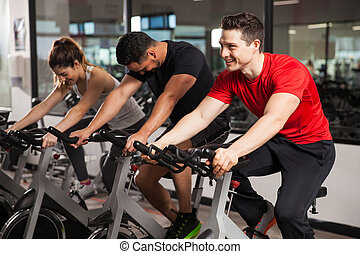 Three people doing spinning in a gym - Group of three people...