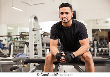 Handsome personal trainer in a gym
