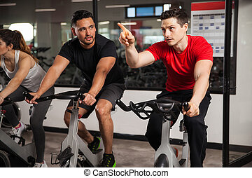 Male friends doing cardio on a bicycle - Young male friends...