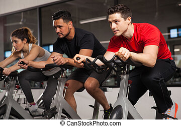 Three people doing cardio on a bicycle - Group of three...