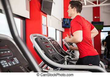 Young man exercising on a treadmill - Profile view of a...