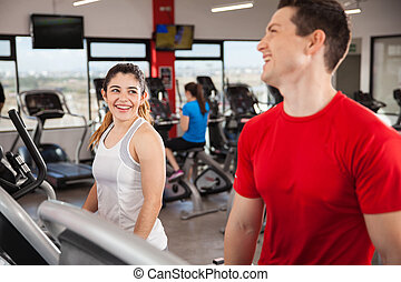 Young couple flirting at the gym - Beautiful young brunette...