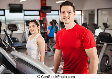 Good looking couple exercising at the gym - Portrait of a...