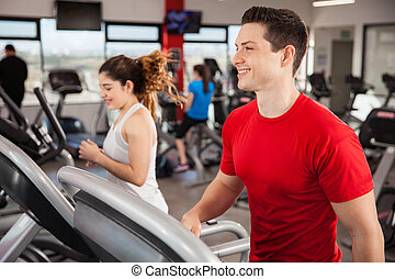 Happy young man jogging at the gym - Good looking young man...