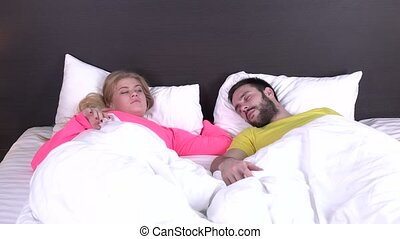 Young couple waking up fully rested, girl wakes up first,...