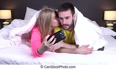 Couple taking selfies in their bedroom, great blonde with...
