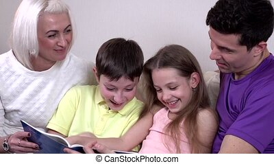 Hapy young family watching a book at home