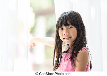 Happy Asian girl holding white curtain at home with copy space.