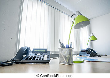 Office desk with a phone and green lamps