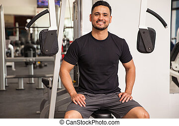 Man enjoying his visit to the gym - Handsome Latin young man...