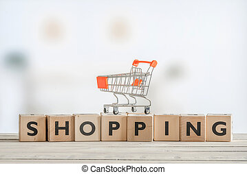 Shopping cart on a wooden sign - Orange shopping cart on a...