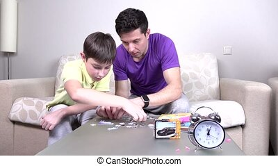 Father and child make puzzle on the table, beige sofa,...