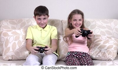 Brother and sister playing video games lying on the couch,...