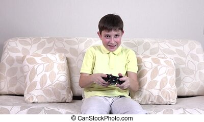 Boy sitting on sofa and palying with joystick, boy dressed...