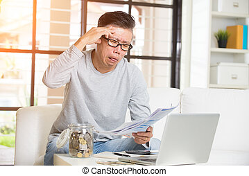 asian matured male paying bills online looking worried