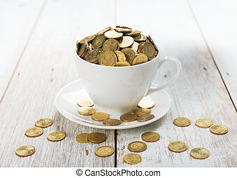 cup of coffee with gold coins of malaysian ringgit