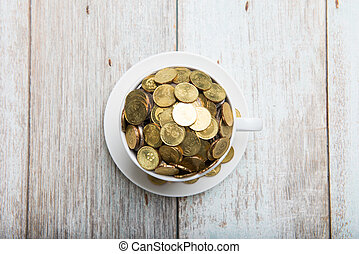 gold coins on a coffee cup top down view
