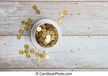gold coins on coffee cup