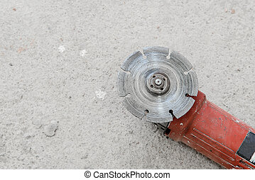 Electric angle grinder at construction building site during...