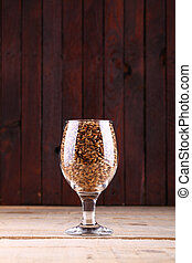 Malt in a glass - Glass full of barley malt over a wooden...