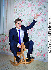 Childish businessman with toy horse - Happy childish young...
