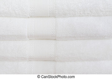 White Towels - White cotton towels stacked on top of each...
