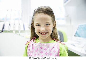 Relaxed little girl at dental office, smiling and waiting...