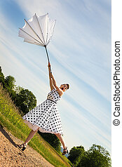 Pin up Girl with a umbrella is blowing off the path - pretty...