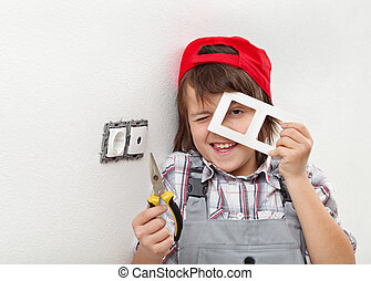 Young boy disassembling an electrical wall fixture