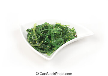 Seaweed salad in a white plate on a light background