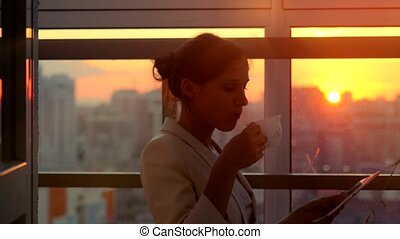 Woman using tablet and drinks coffee with sunbeams and lens flare Business girl young adult against sunset sky window. 4k