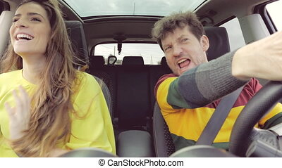 Couple screaming against traffic laughing driving car slow...