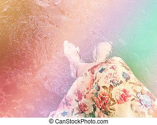 Women in flowers dress sit and dip feet in water - Dreamy...